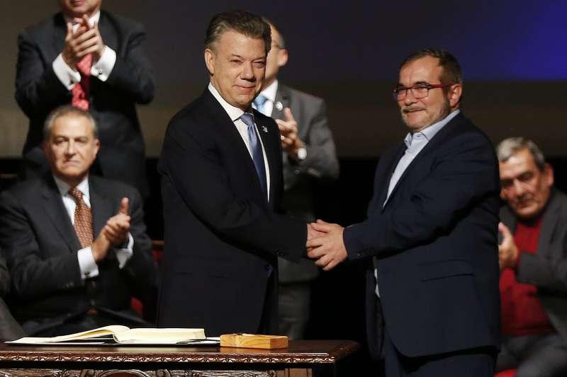 哥倫比亞總統桑托斯(左)與FARC領袖隆多尼歐(右)簽訂新版和平協議後握手(AP)