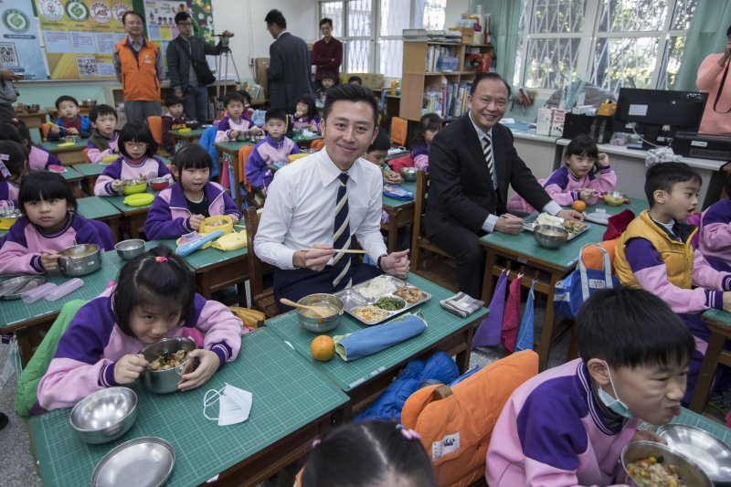 新竹市長林志堅(前)和農委會主委林聰賢(後),與新竹市三民國小學童共進營養午餐。(新竹市政府提供)