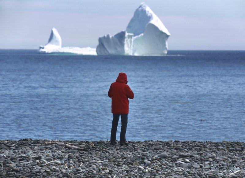 加拿大紐芬蘭外海出現一座「擱淺」的冰山,許多人爭相跑來拍照。(美聯社)