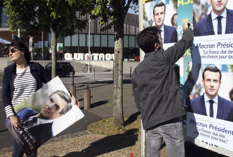 法國總統候選人費雍的支持者用費雍的海報蓋住另一位候選人馬克宏的海報(AP)