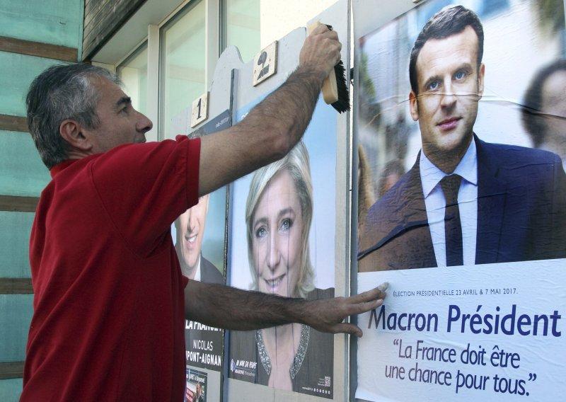 法國總統候選人馬克宏的支持者用馬克宏的海報蓋住另一位候選人勒潘的海報(AP)