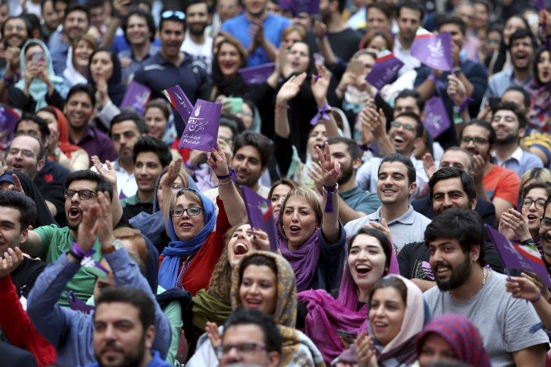 伊朗總統候選人魯哈尼的支持者,手持象徵魯哈尼的紫色旗幟。(美聯社)