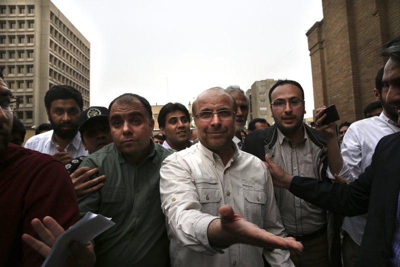 伊朗總統候選人之一(白衣者)15日宣布棄選,轉為支持保守派候選人萊希。(美聯社)