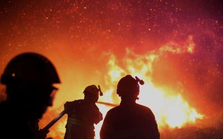 法國科西嘉島的消防人員正在灑水滅火(AP)