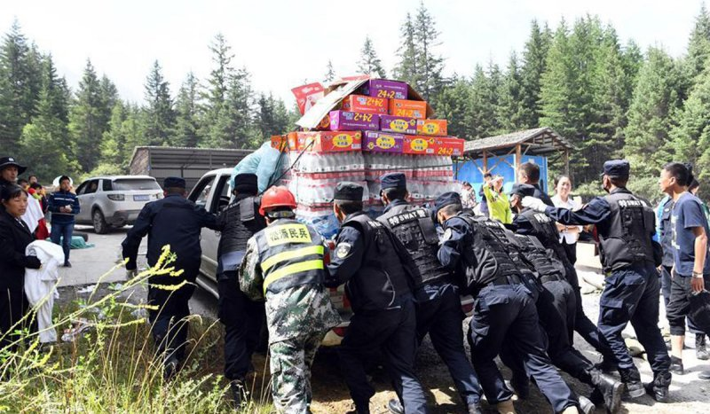 九寨溝強震後,救難隊與志工運送物資。(新華網)