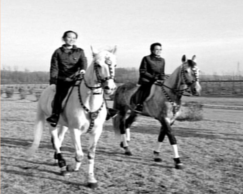 騎著白馬的金與正,還有在後頭騎著灰馬的金敬姬,兩人都露出開朗的笑容。(八旗文化出版社提供)