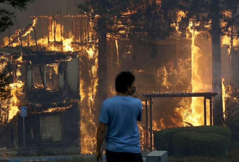 加州索諾瑪的希爾頓飯店也被燒毀,一名住客在旁邊望著大火吞噬建築(AP)