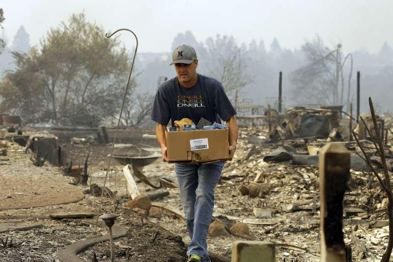 10月9日,住在加州聖羅莎方廷格羅夫(Fountaingrove)社區的一名男子回家取沒被烈火吞事的財產(AP)