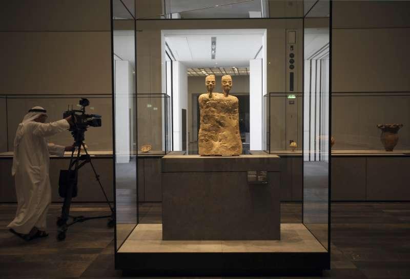 攝影之正在拍攝阿布達比羅浮宮展出的約旦雙頭人雕像,約創作於西元前6500年。(美聯社)