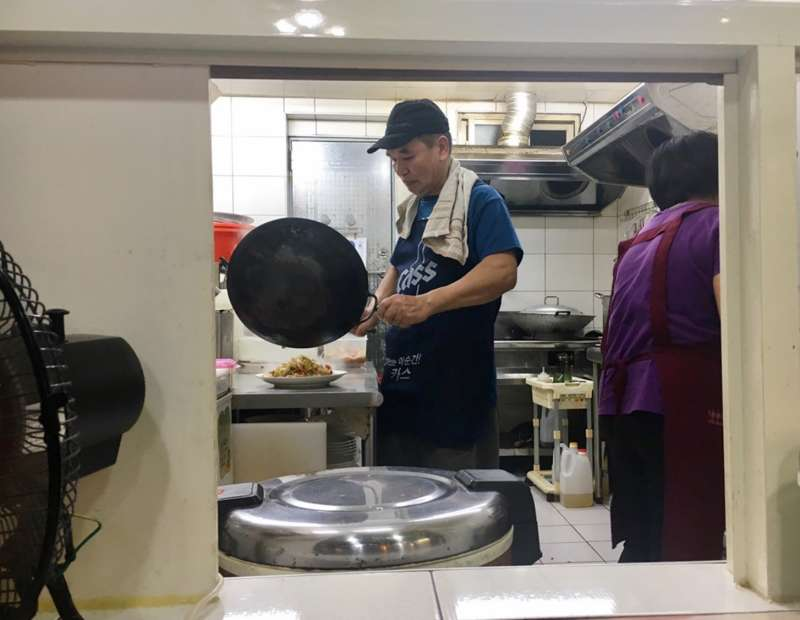 小小廚房裡,老闆侯丙木的身影竄來竄去,一下洗碗、一下又炒菜。(圖/鐘敏瑜攝)