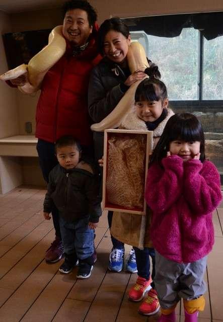 抽中1等獎黃金蟒蛇皮的高田一家,與活生生的黃金蟒一起拍攝紀念照。(圖/潮日本提供)