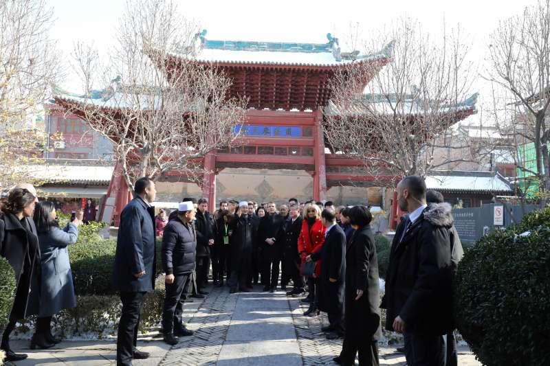 法國總統馬克宏(中)偕夫人布莉姬特(紅衣者)8日訪問中國西安的大清真寺(AP)