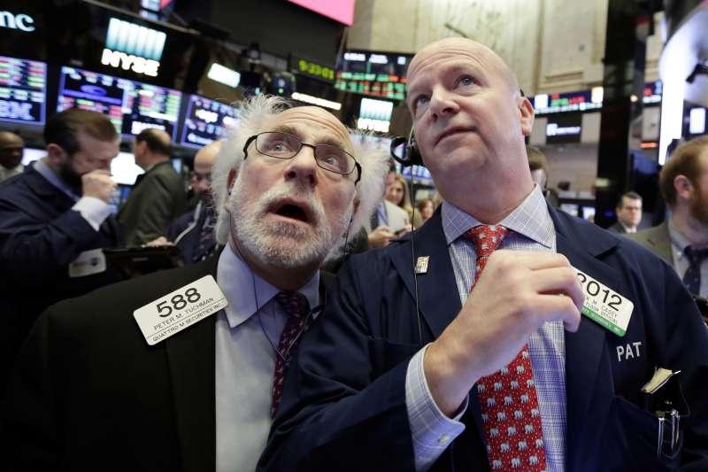 美股8日再度重挫超過千點,紐約證交所裡的交易員緊盯盤勢。(美聯社)