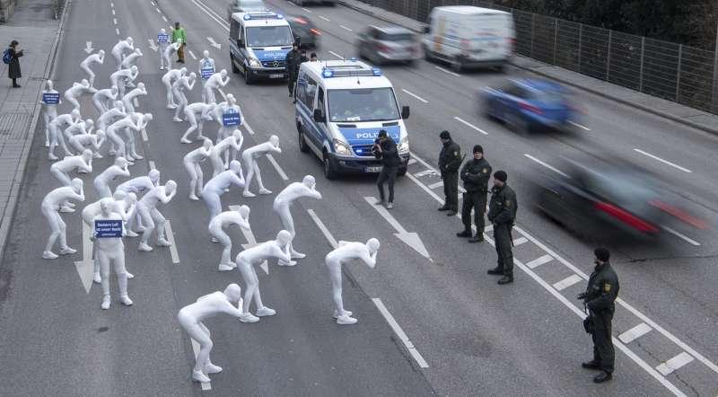 綠色和平(Greenpeace)成員占據車道,抗議汽車的廢氣汙染空氣。(美聯社)