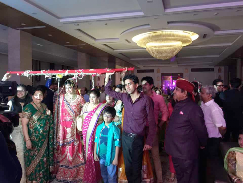 20170308-印度新娘在婚宴上出場時,娘家親戚會用一條華麗的紗幔罩護她走入新人花座,作用有點像台灣新娘從娘家出閣走上禮車前使用的米篩。(作者提供)