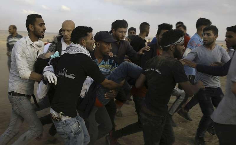 人們焦急地搶救中槍的納吉兒。(AP)
