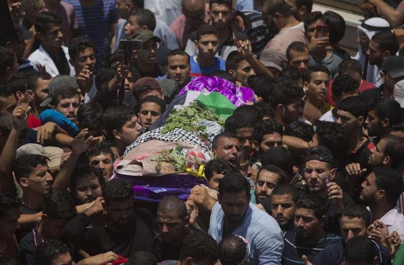 送納吉兒最後一程的群眾擠滿了整條街,她的遺體被巴勒斯坦國旗覆蓋。(AP)