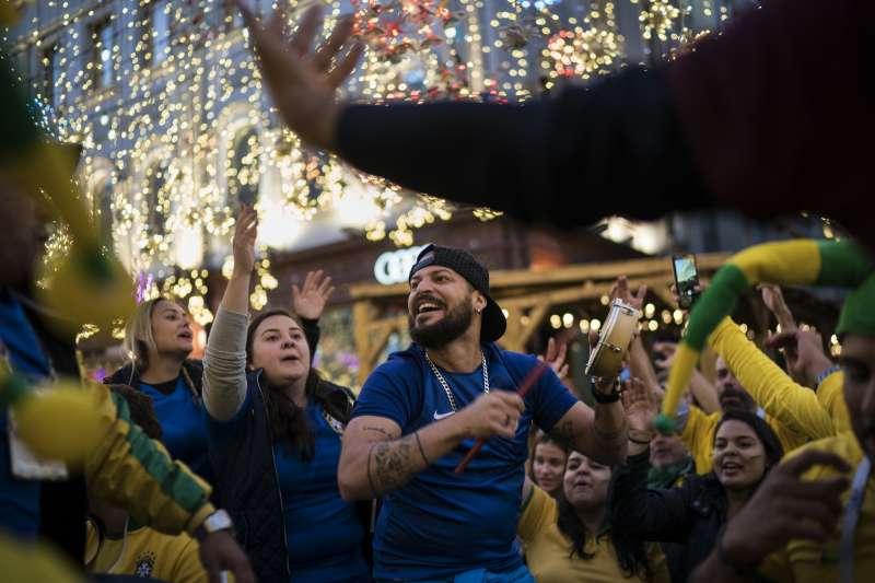 6月13日晚間,來自巴西的球迷聚集在俄羅斯莫斯科尼科斯卡亞街,與其他國家的球迷一起開心慶祝(美聯社)