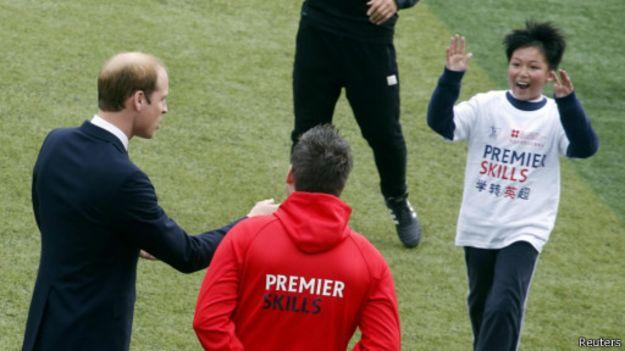 一名正在練球的中國孩子熱情地跑上前去和威廉王子擊掌。(BBC中文網)