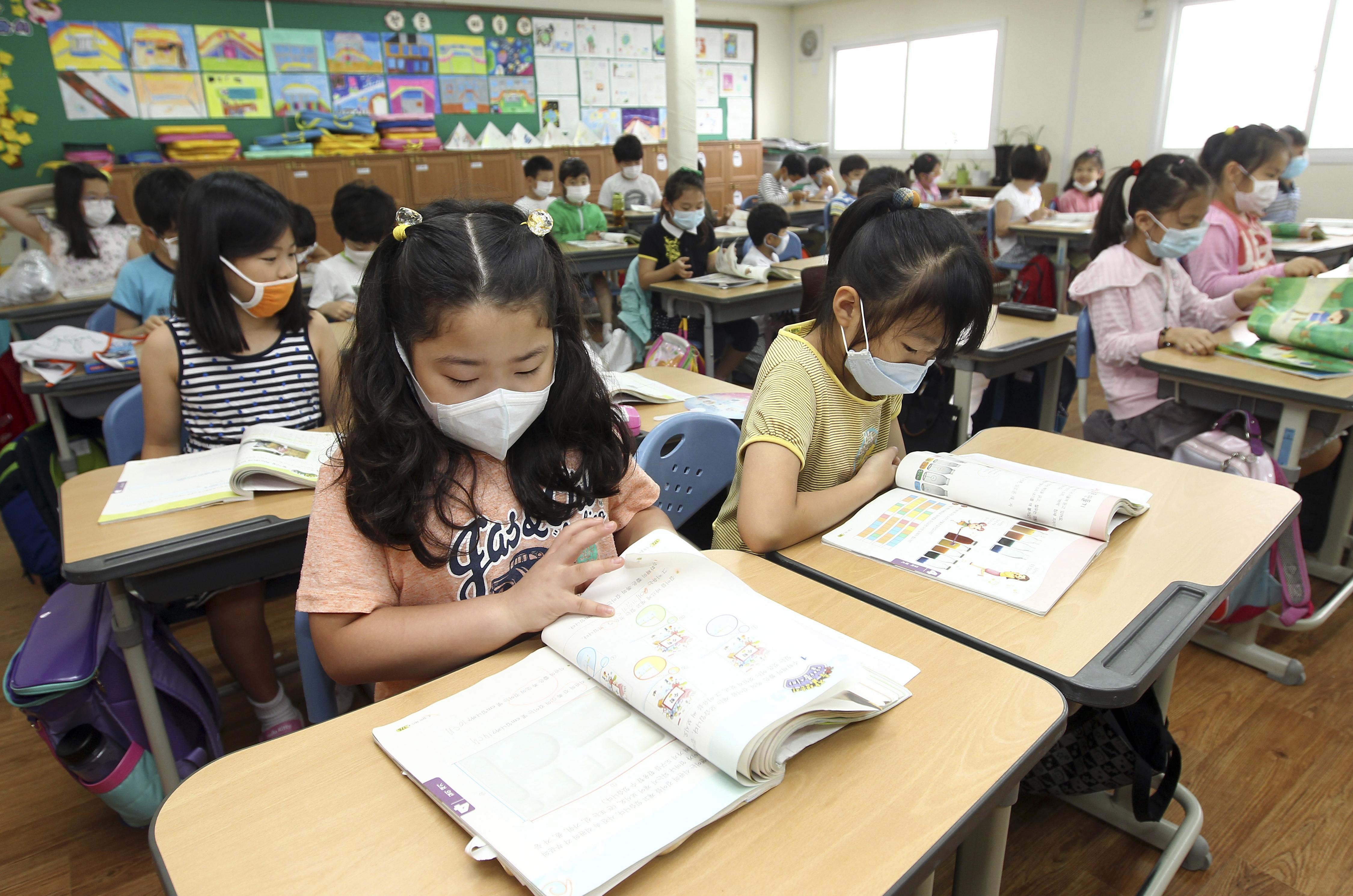 釜山的南韓小學生22日戴著口罩上課。(美聯社)