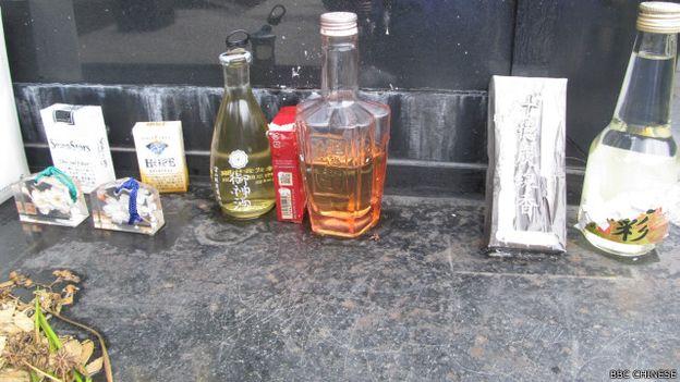 從紀念碑前的供品來看,不少是從日本捎來的,例如正中間那瓶有「靖國」刻印的酒(BBC中文網照片)。