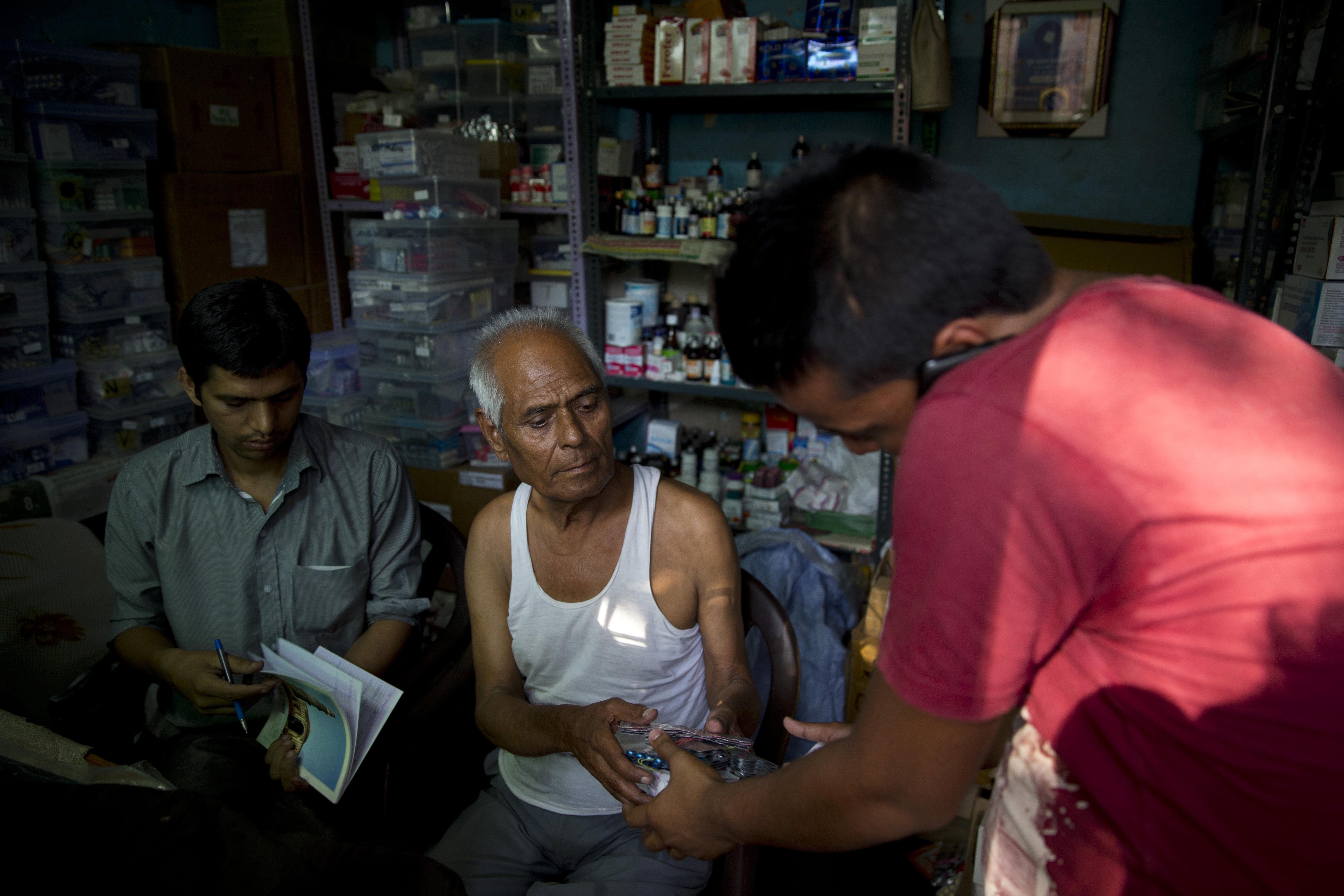「醫藥巴巴」(Baba)翁卡納斯(Omkarnath)和拿藥的病患家屬(美聯社)