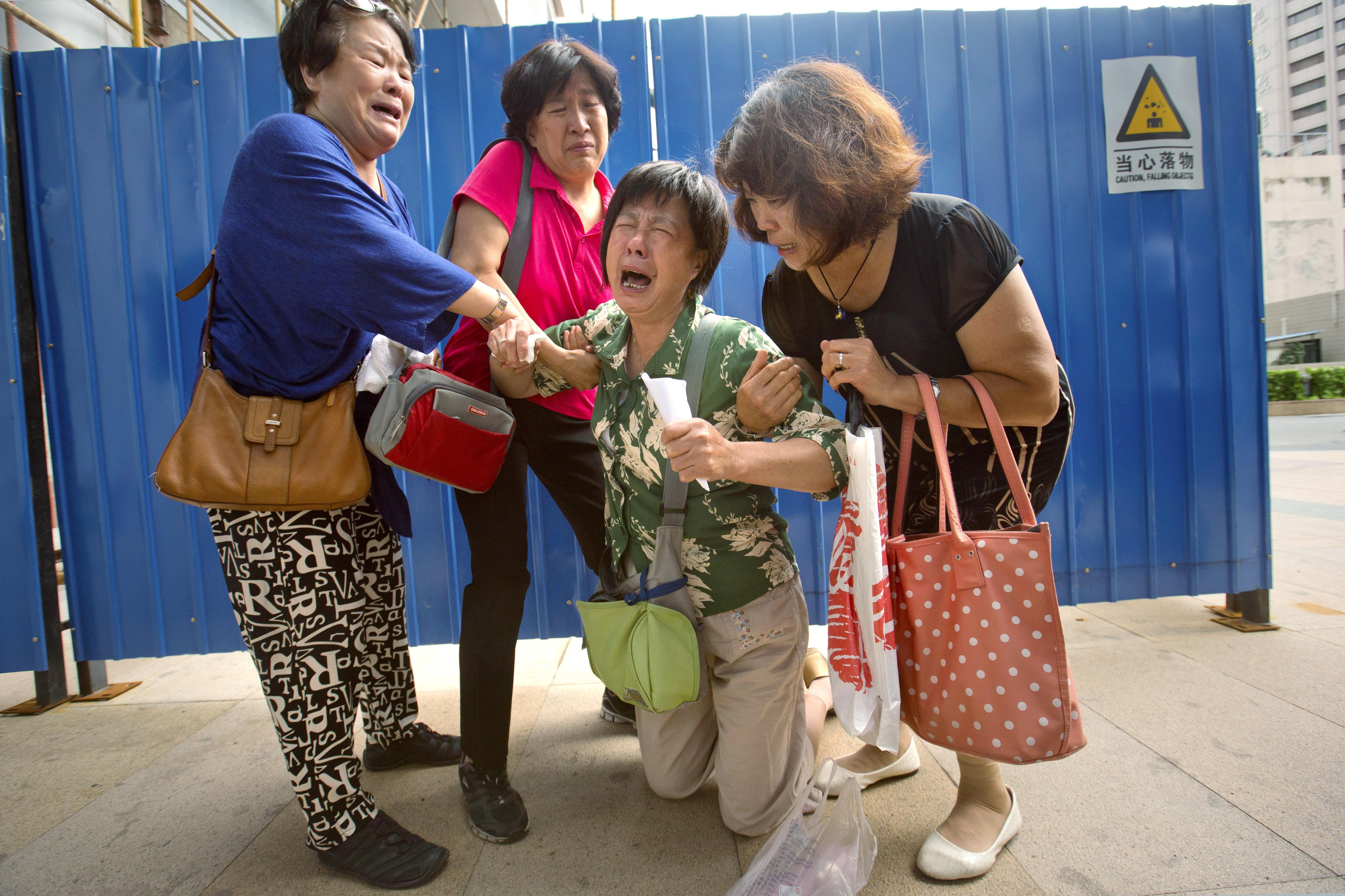 北京一位老婦人的兒子、媳婦與孫輩都在MH370上,想到她永遠回不來的親人,情緒再度潰堤。(美聯社)