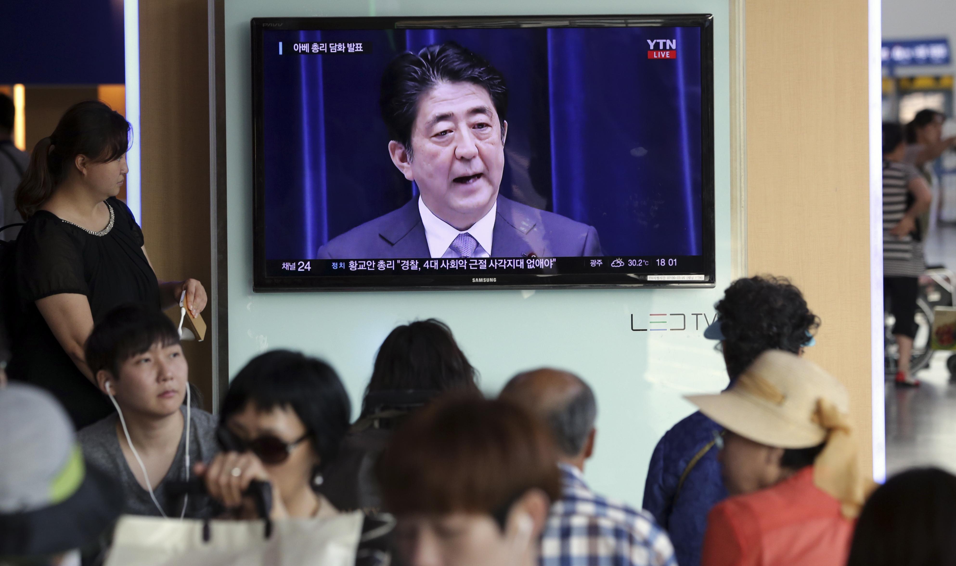 南韓民眾收看安倍談話。(美聯社)
