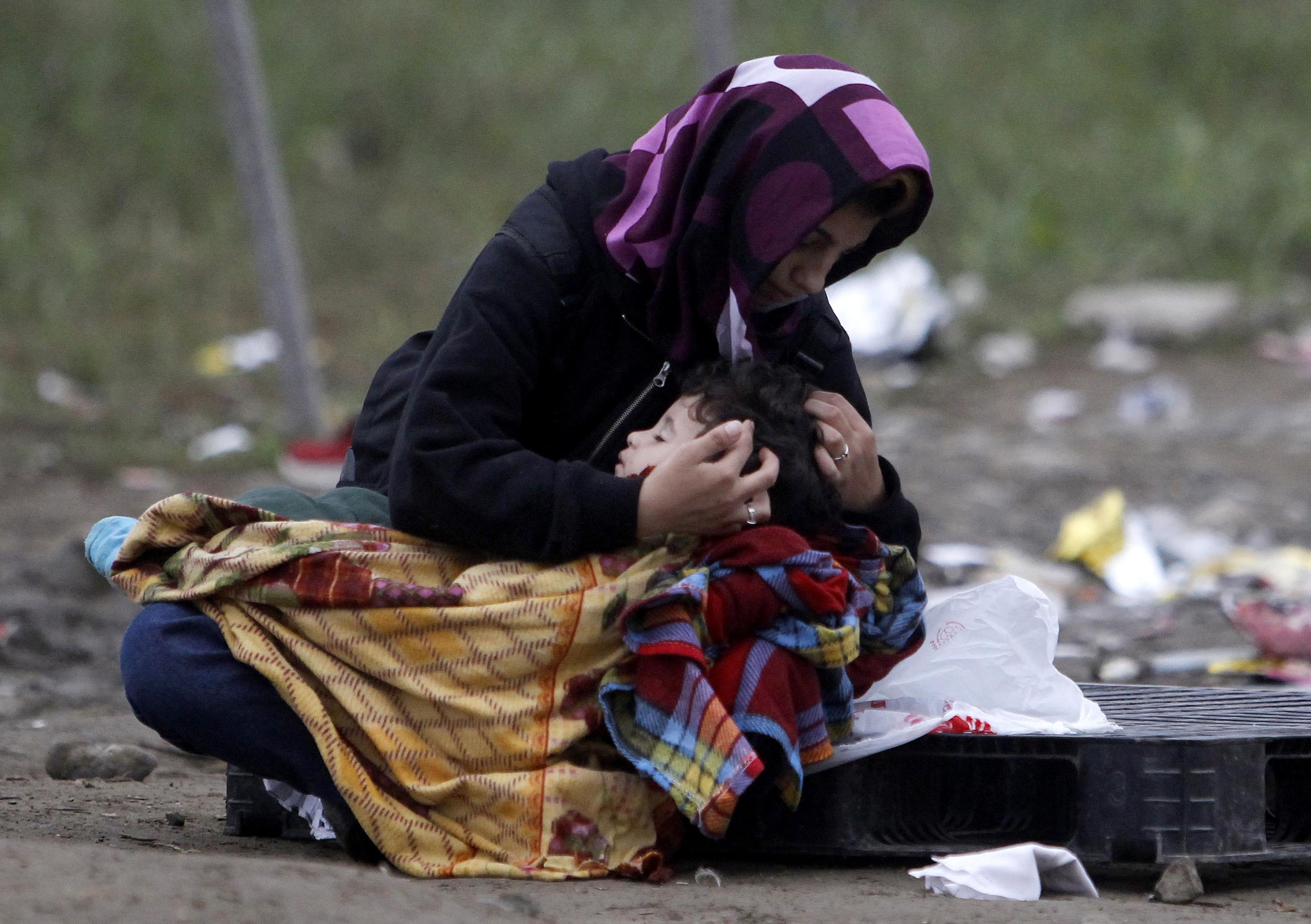 馬其頓難民營裡,一位女性輕柔地哄著孩子入睡。(美聯社)