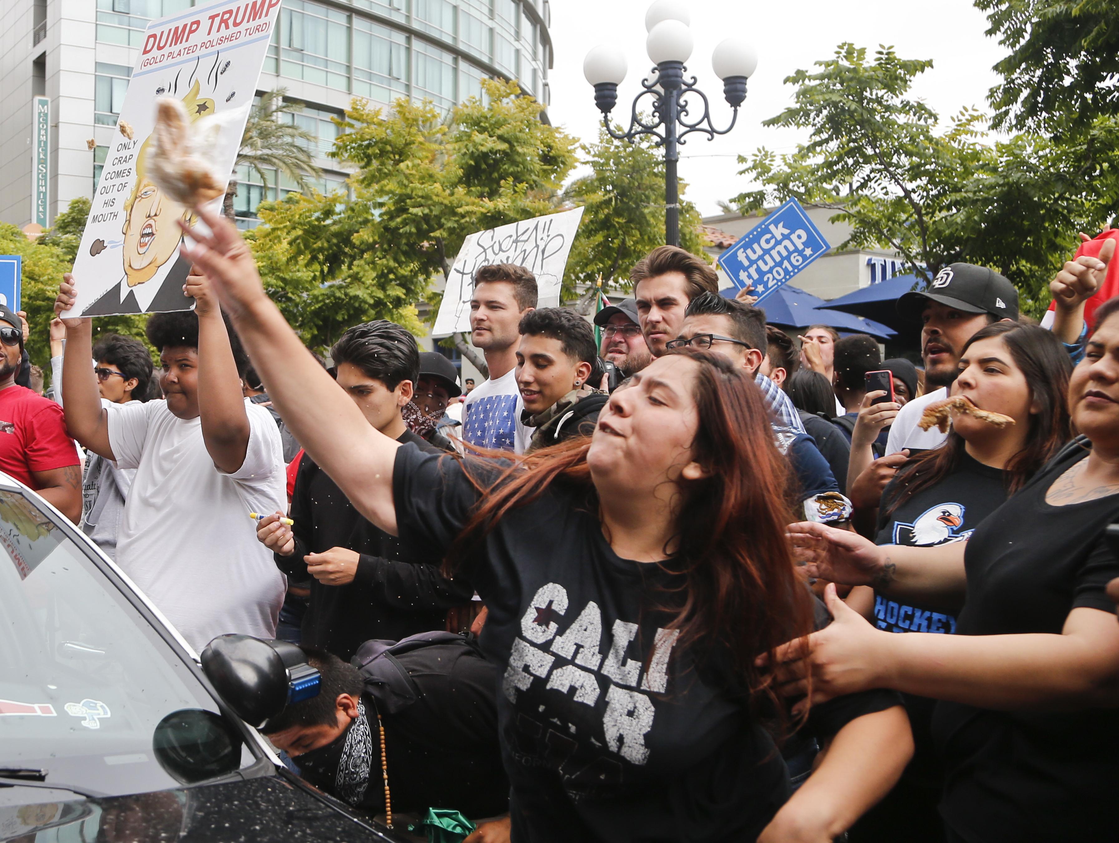 聖地牙哥的抗議民眾向對手陣營丟擲雜物。(美聯社)