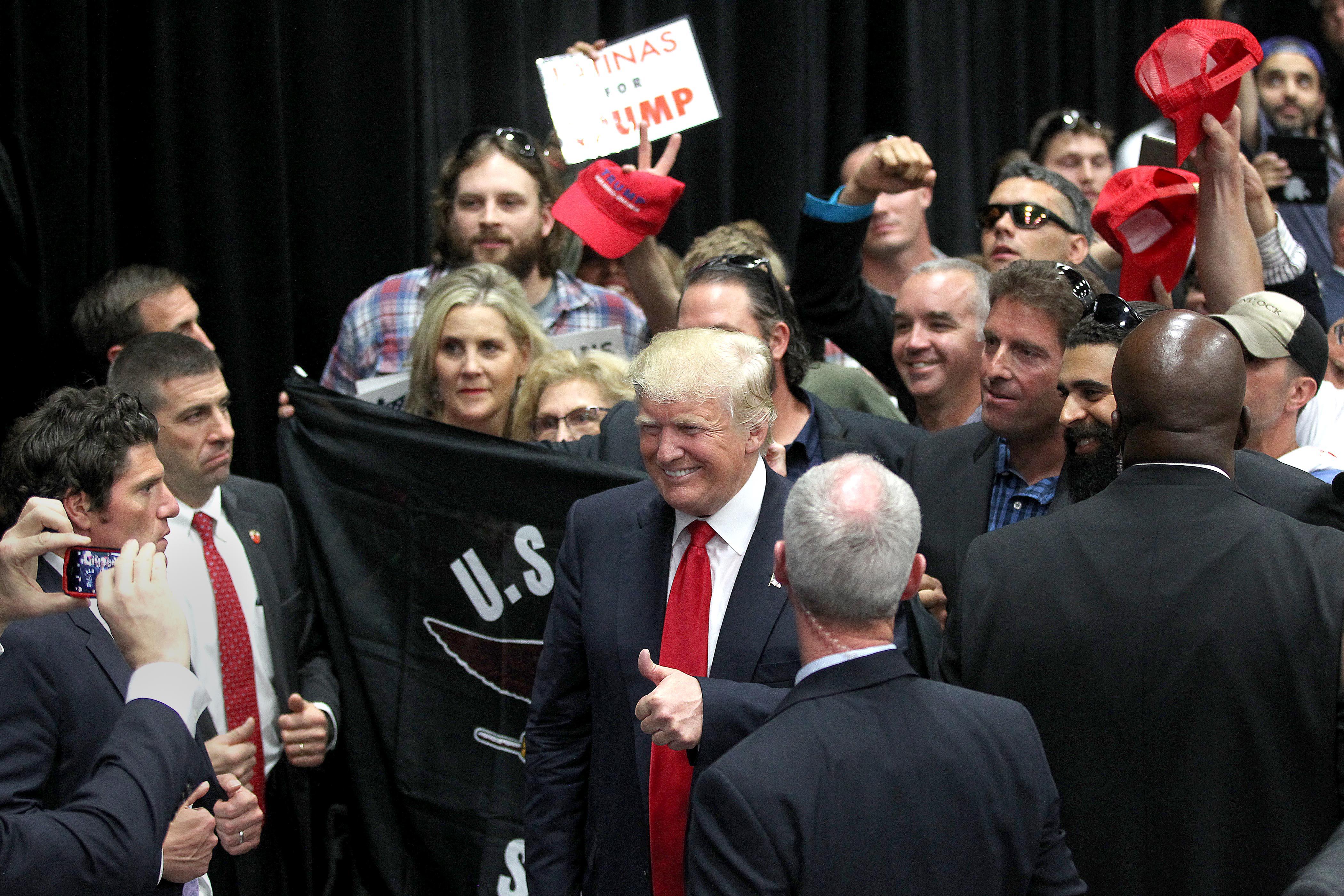 川普在支持者簇擁下,準備離開聖地牙哥的演講會場。(美聯社)