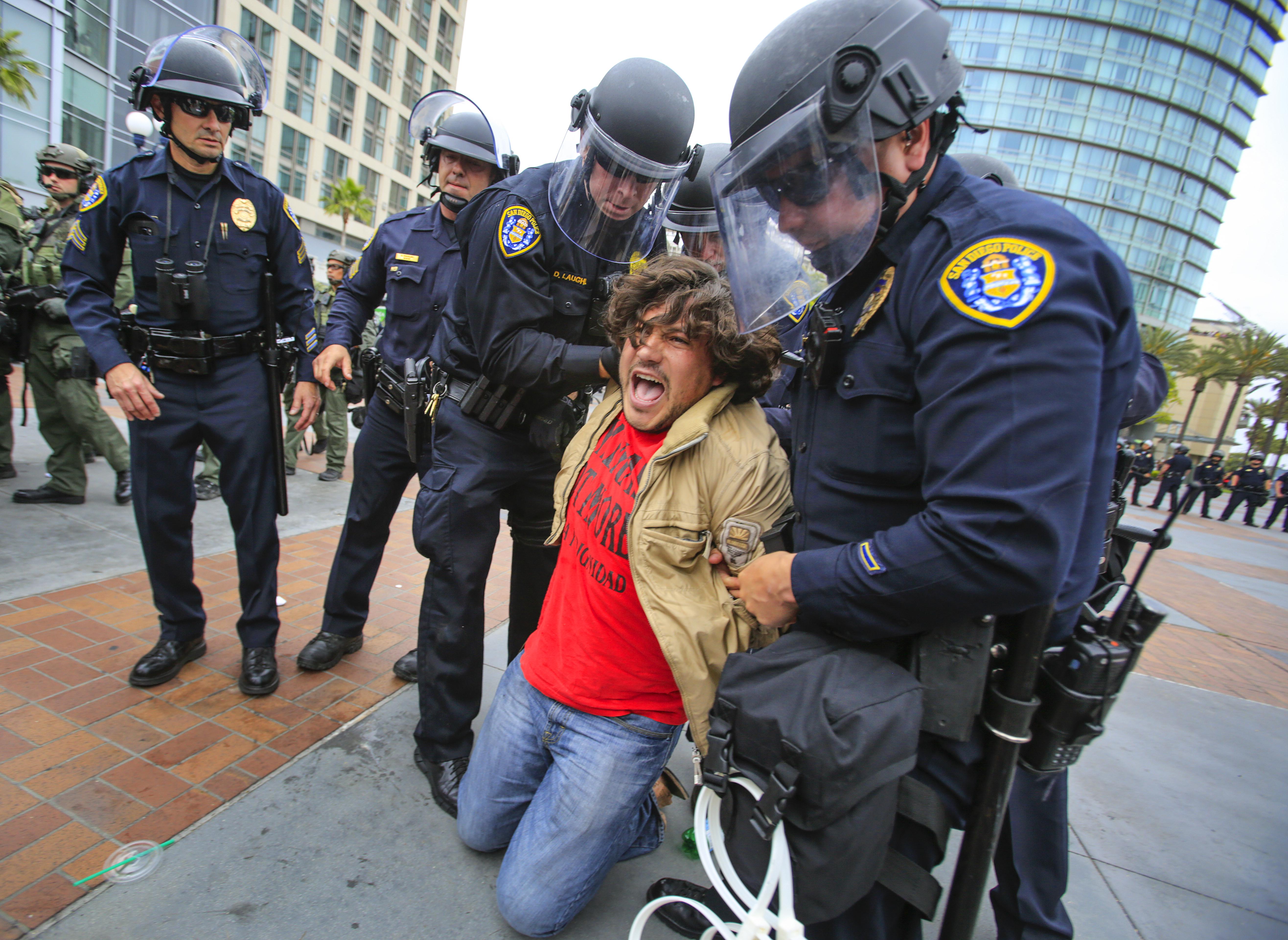 在川普演說的會場外,警方逮捕激烈示威抗議的民眾。(美聯社)