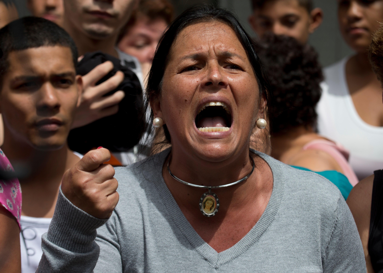 一位憤怒的婦女2日在委內瑞拉總統府外大喊「罷免!」(美聯社)