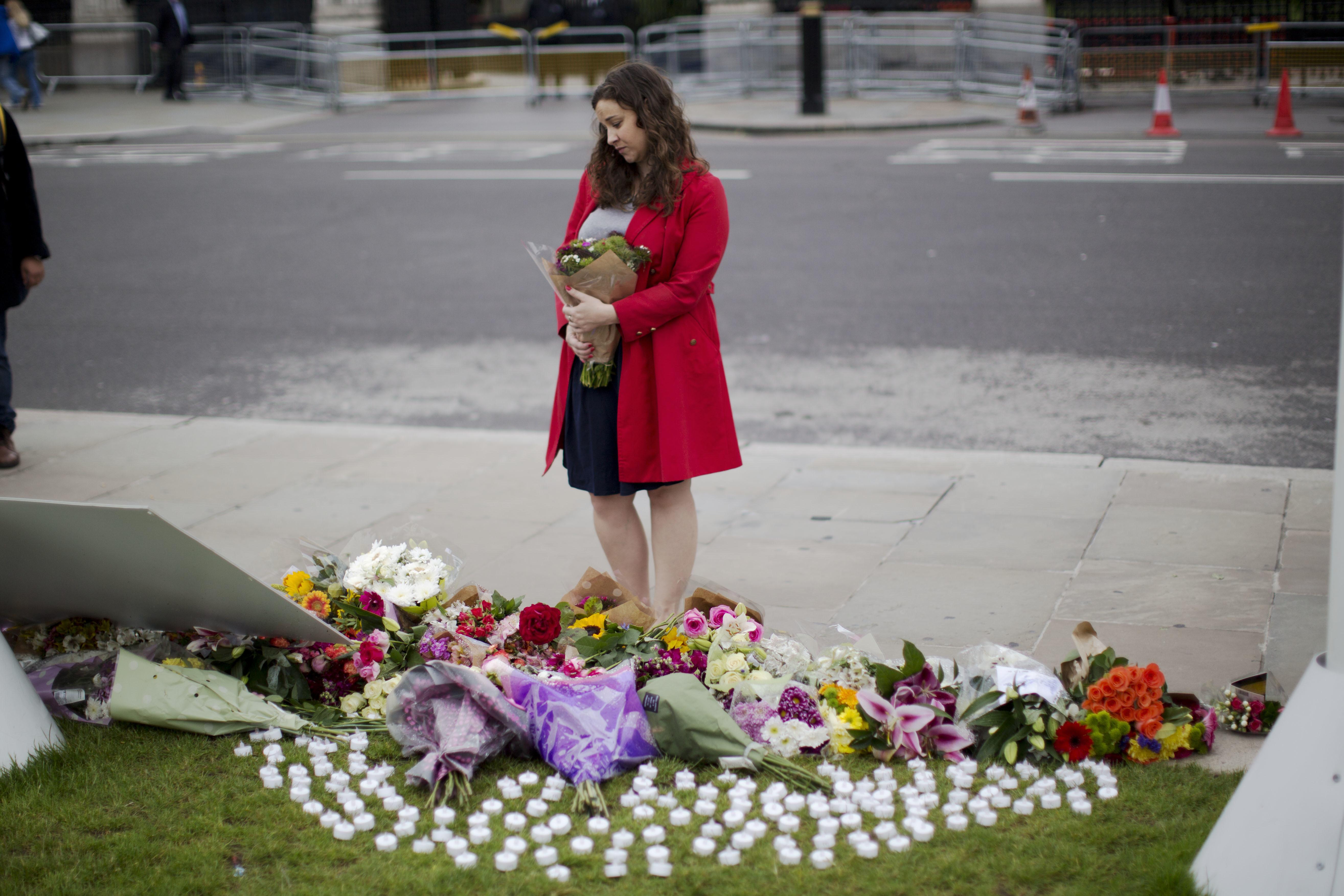 哀傷的民眾為遇刺的英國國會女議員柯克斯(Jo Cox)獻花。(美聯社)