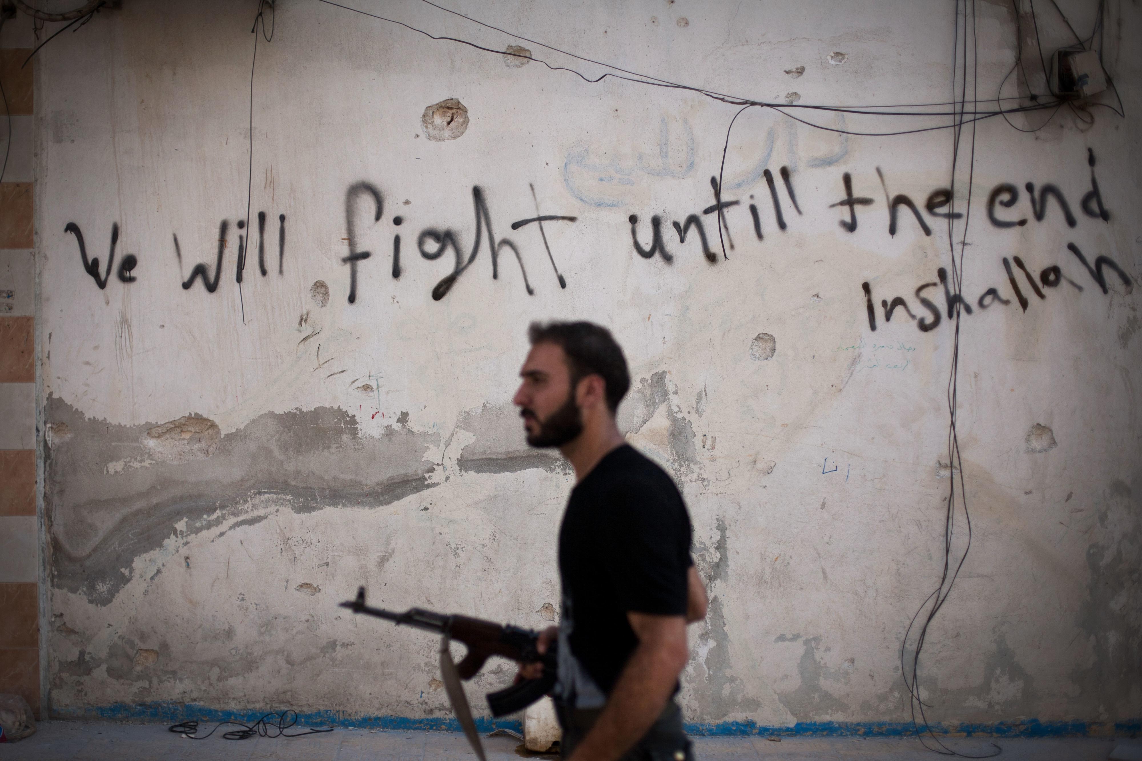 敘利亞北部大城阿勒坡戰火頻仍,一面牆上有人用英文寫著「我們會奮戰到最後—如果神允許的話」。(美聯社)