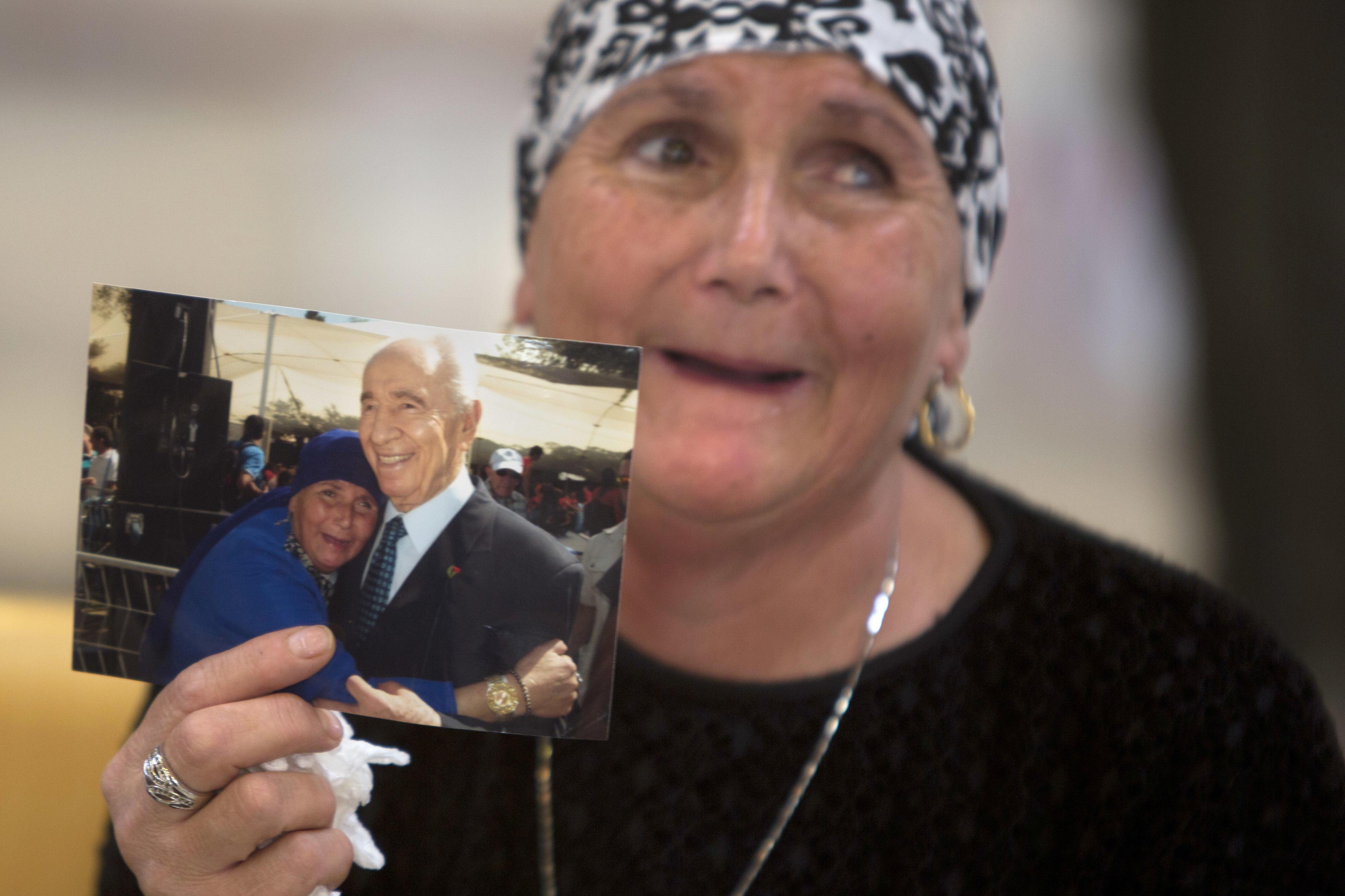 一位以色列婦女拿出她與前總統裴瑞斯的合照,祈求裴瑞斯能早日康復。(美聯社)