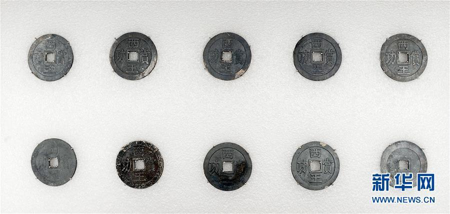 考古隊挖掘出的「西王賞功」銀幣。(新華社)