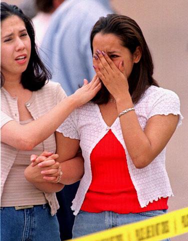 科倫拜高中的高二生克利斯汀(右)幸運逃離血腥屠殺,但忍不住傷心流淚,她的友人凱西安慰著她(AP)