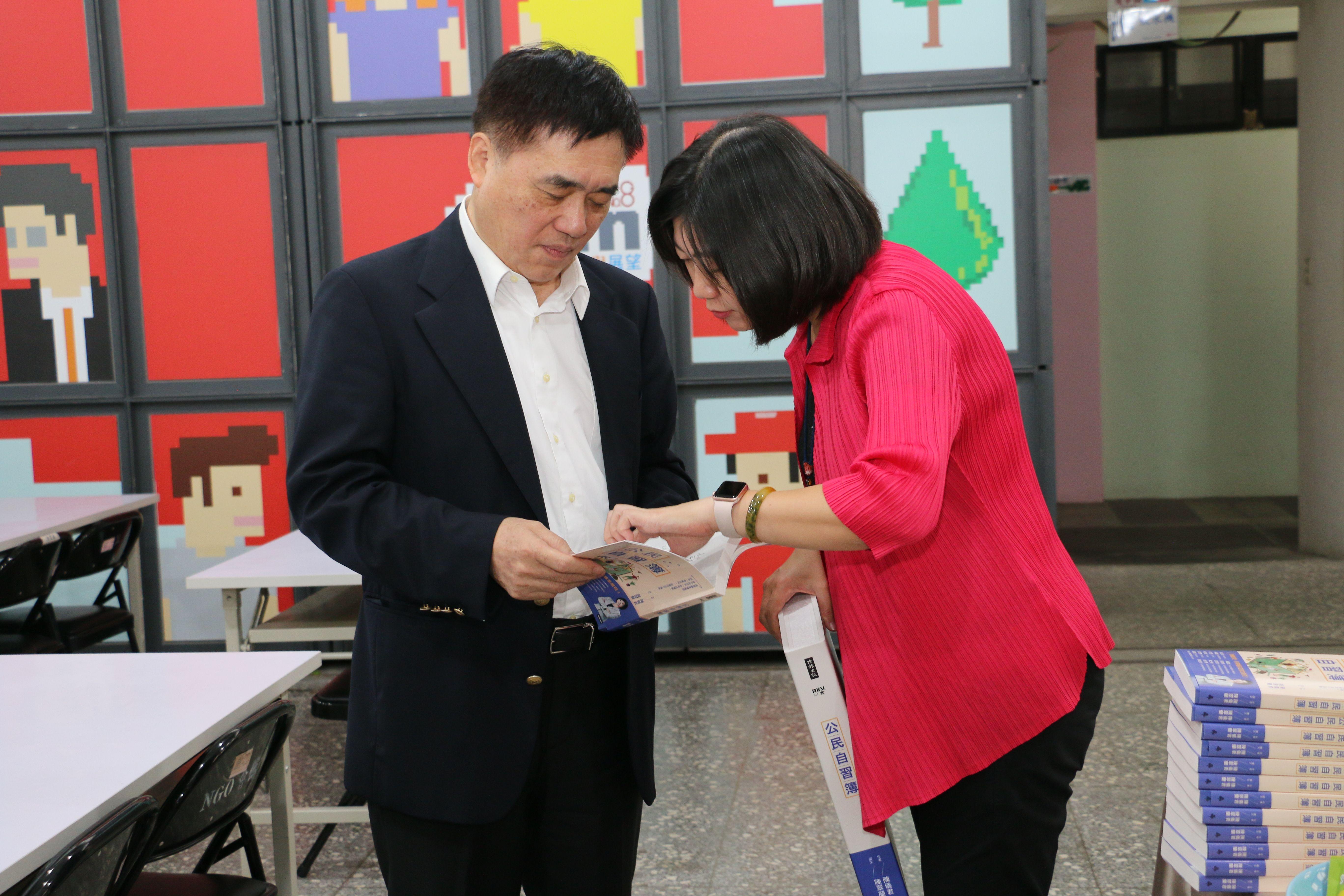 國民黨副主席郝龍斌(左)認真翻閱《公民自習簿》內容。(圖/李梅瑛攝)