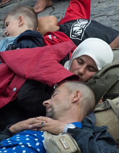 經由匈牙利轉往奧地利的一家難民,在慕尼黑中央車站的難民接待中心席地而眠,等待轉車。(美聯社)