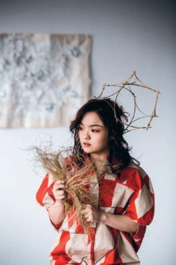 佈滿幾何圖形的服裝,頭上的工藝裝飾往留白的植物背景延伸(頭飾為李霽個人收藏之日籍設計師作品)