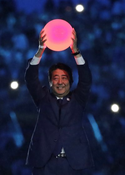 安倍舉起發光的紅色圓球,象徵日本國旗上的太陽圖案。(美聯社)