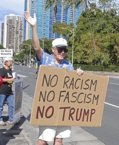 夏威夷一位民眾在州議會外舉牌,高呼「不要種族主義、不要法西斯、不要川普!」(美聯社)