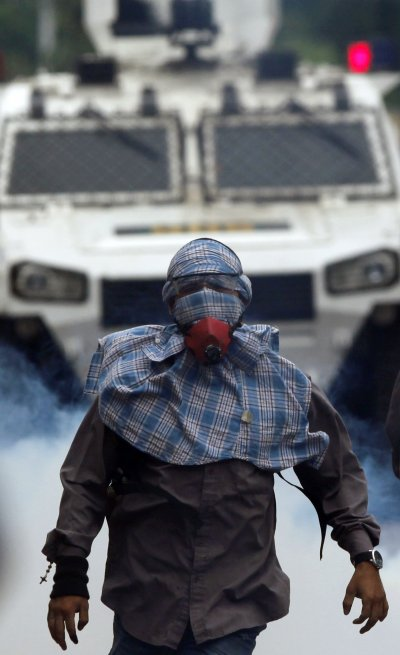 一名反馬杜洛修憲的委內瑞拉民眾在街頭抗議,他身後是軍警對抗民眾的裝甲車。(美聯社)