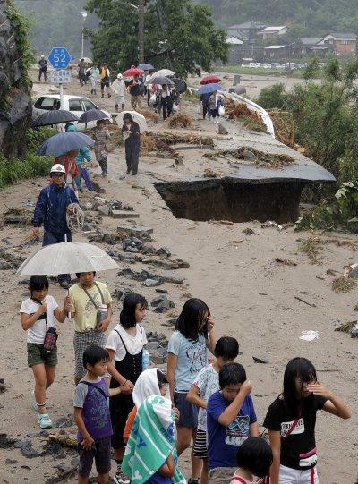 日本大雨成災,福岡縣朝倉市的災民被緊急疏散,畫面中的山路路基已被掏空。(美聯社)