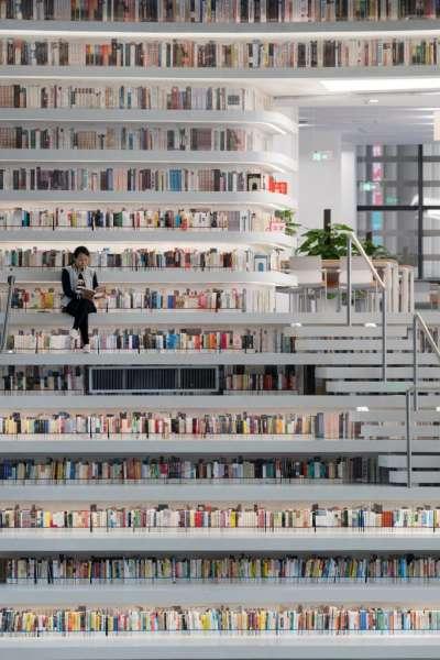 書架在規劃上,是可以坐下閱讀的好地方,同時也是為了可以進入上層的過道設計。(圖/dezeen,瘋設計提供)