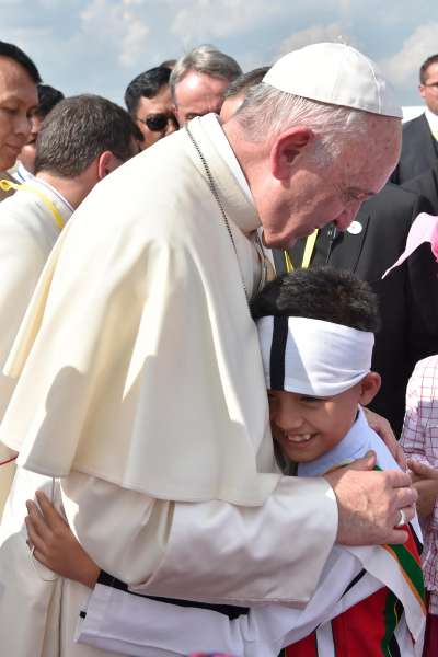 天主教教宗方濟各27日抵達緬甸仰光,一名小男孩開心抱住他(美聯社)