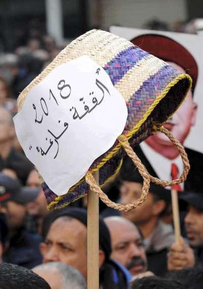 突尼西亞最新撙節措施造成物價大漲,圖中民眾高舉籃子,字條寫著「籃子空空」。(美聯社)