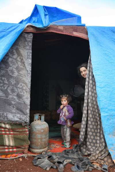 敘利亞兒童從充當新家的帳篷往外望。毯子和塑膠布是抵禦寒冬的僅有材料。煤氣罐提供熱能,但在帳篷內使用並不安全。© Omar Haj Kadour/MSF