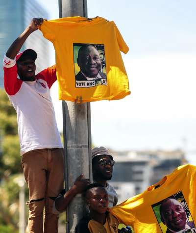 南非總統祖馬辭職,由副總統拉馬福薩繼任,民眾高舉印有拉馬伏薩肖像的衣服。(美聯社)